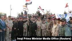 Премьер-министр Ирака Хайдар аль-Абади держит в руках государственный флаг