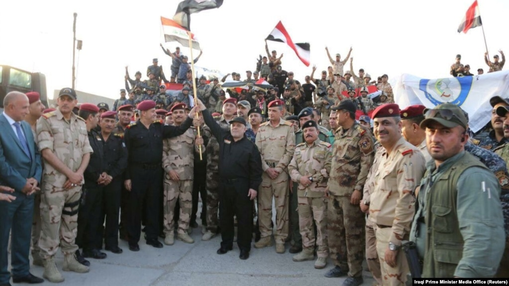 Iraqi Prime Minister Haidar al-Abadi holds an Iraqi flag as he declares victory over IS in Mosul on July 10.