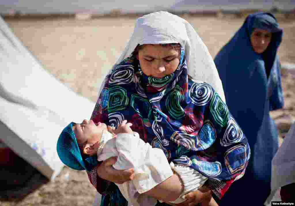 Homayra, a widow carrying her paralyzed child, lives in a makeshift refugee camp outside Mazar-e Sharif, Balkh Province.