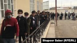 مهاجرینی که از ایران برگشته اند در قطار ایستاده اند تا پس از معاینه صحی در سرحد اسلام قلعه به طرف شهر هرات حرکت کنند. March 17 2020