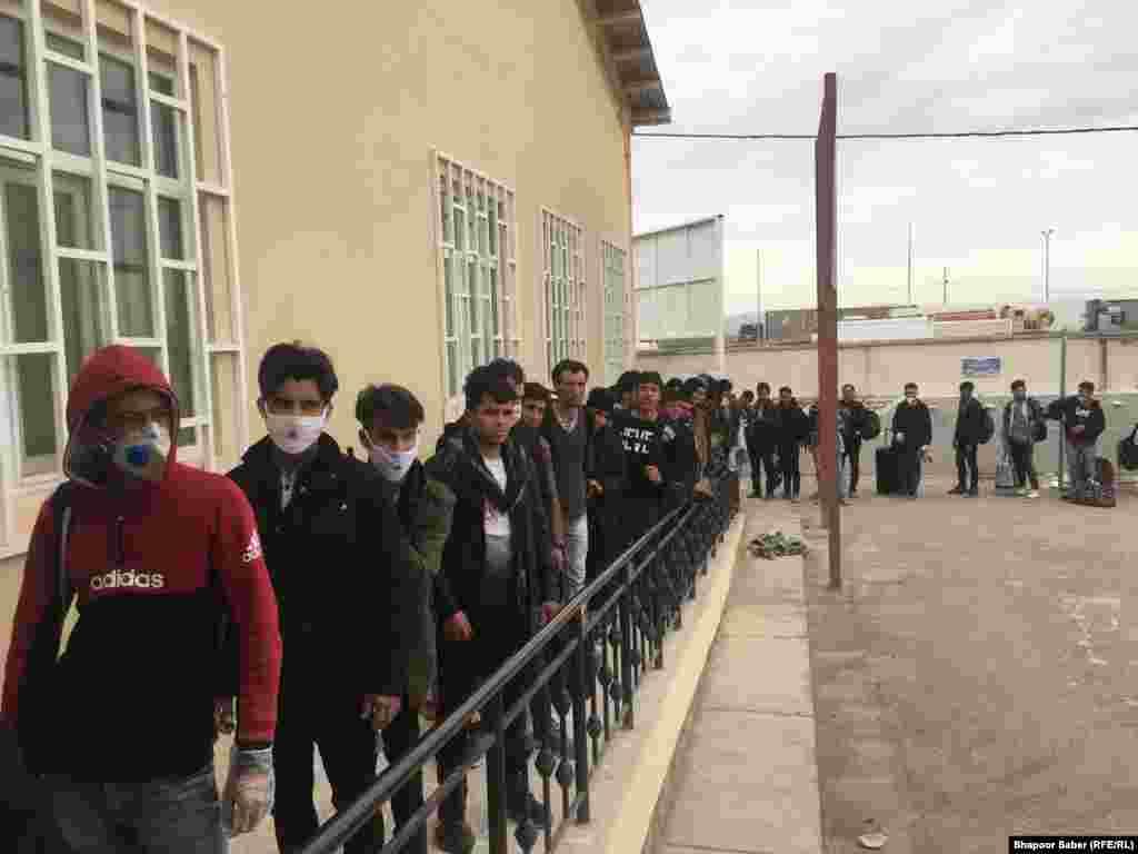 افغان هایی که از ایران برگشته اند در یک صف طولانی در مرز اسلام قلعه انتظار اند تا پس از معاینه صحی به سوی شهر هرات حرکت کنند.