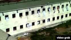 Арестанты машут простынями с надписью из окон СИЗО. Сцена тюремного бунта. Актобе, 11 июля 2012 года.
