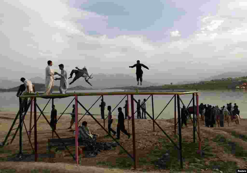 Afghans play on a trampoline along Qargha Lake on the outskirts of Kabul on April 28. (Reuters/Mohammad Ismail)