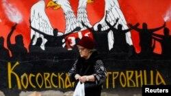 Женщина идет по улице в городе Косовска-Митровица на севере Косово.