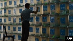 An Afghan election commission worker takes a note of sealed ballot boxes during an audit of the presidential run-off vote in the country's general election at a counting center in Kabul. (file photo)