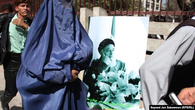Supporters carry portraits of Burhanuddin Rabbani during a gathering in Kabul to remember him.