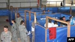 АҚШ әскерилері дәрігерлерге Эболадан қорғайтын биологиялық киімді дұрыс киюді үйретіп жатыр. Либерия, 9 қараша 2014 жыл.