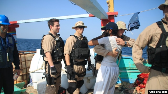 """A U.S. Navy image of a """"USS Kidd"""" crew member embracing one of the fishermen whose Iranian-flagged """"Al Molai"""" vessel and crew were saved from pirates on January 5 in the northern Arabian Sea."""