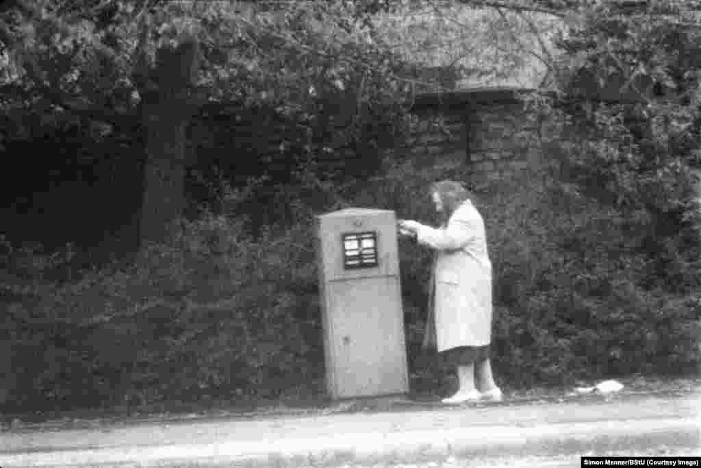 An elderly woman posting a letter on a winter day in communist East Germany (GDR).