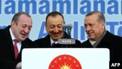 Gürcüstan prezidenti Giorgi Margvelashvili (solda), Azırbaycan prezidenti İlham Əliyev (mərkəzdə) və Türkiyə prezidenti Recep Tayyip Erdogan Qarsda TANAP layihəsinin imzalanması mərzisimi zamanı Heydər Əliyevin adını daşıyan məktəbin də açılışını edirlər. 17 mart 2015