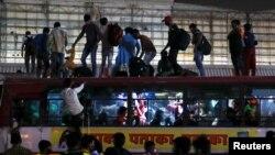 Lucrători care părăsesc New Delhi sunt nevoiți să călătorească pe acoperișul autobuzelor. 19 aprilie 2021