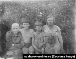 Семейное фото начала 1930-х, на котором Сахаров (второй слева) с братом Георгием; его мать Екатерина (справа) и бабушка Мария Петровна, которой Сахаров воздал должное в заявлении, оглашенном на вручении Нобелевской премии в 1975 году. Он сказал, что «особенно благодарен» ей за память, и вспомнил, как она читала ему произведения классической художественной литературы, включая книги англоязычных писателей, таких как Чарльз Диккенс и Гарриет Бичер-Стоу.
