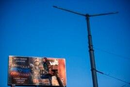 Рабочий клеит предвыборный плакат на бигборд в Макеевке, Донецкая область