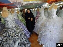 Иранка проходит среди висящих в магазине свадебных платьев.