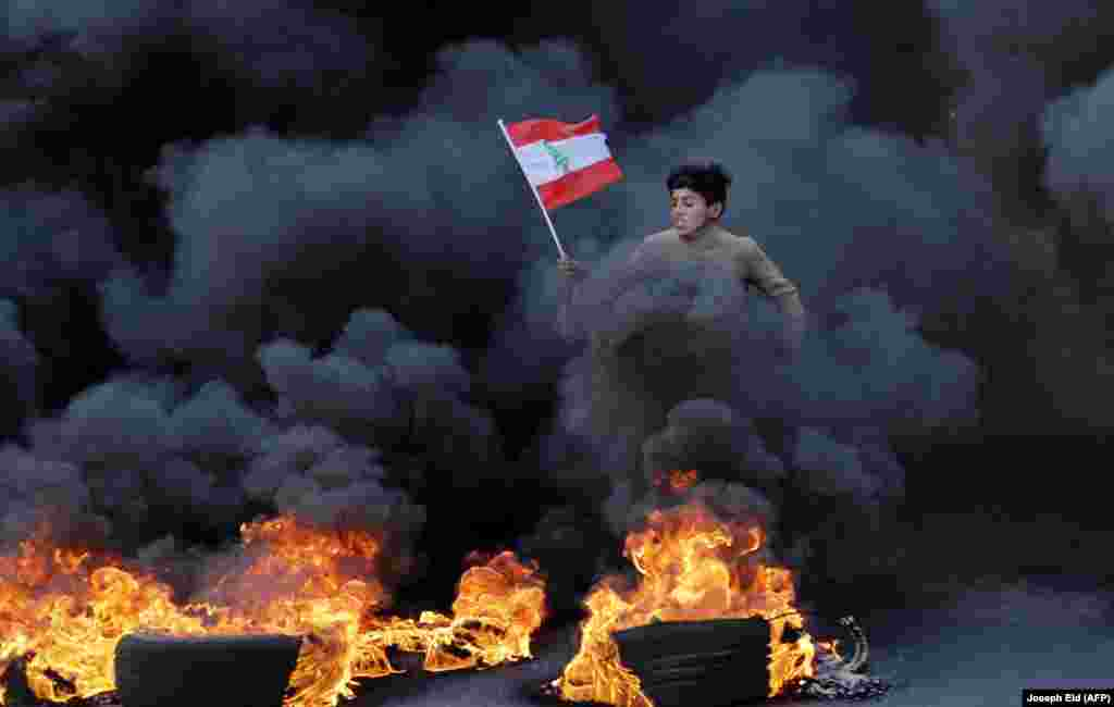 A Lebanese youth runs with a national flag as smoke billows from burning tires during a demonstration on the outskirts of Beirut on January 14. (AFP/Joseph Eid)