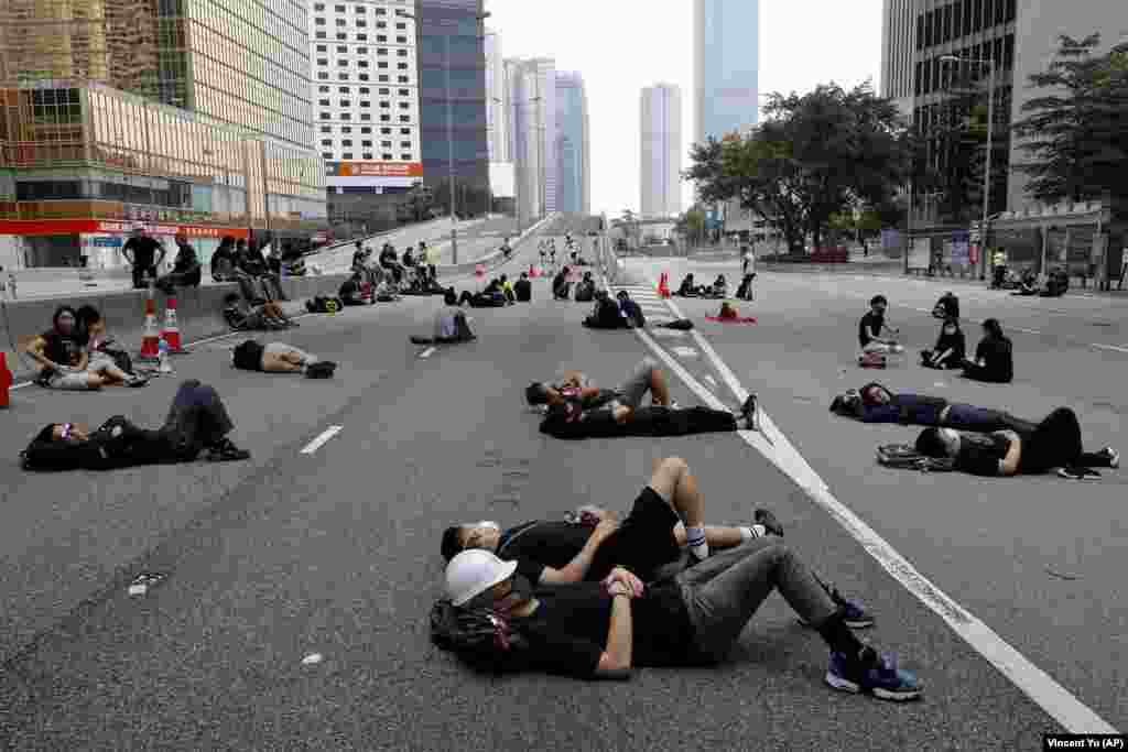 Protesters who camped out overnight take a rest along a main road near the Legislative Council after continuing protests against an unpopular extradition bill in Hong Kong on June 17. (AP/Vincent Yu)