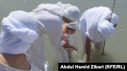 صابئة مندائيون يعمّدون طفلاً في مياه نهر الزاب الكبير قرب أربيل
