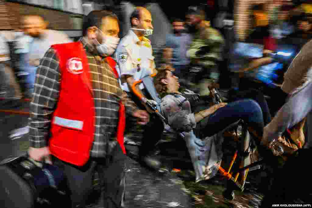 First responders carry away a woman on a wheelchair at the scene of an explosion at the Sina At'har health center in the Iranian capital, Tehran, on June 30. (ISNA-AFP/Amir Kholousi)