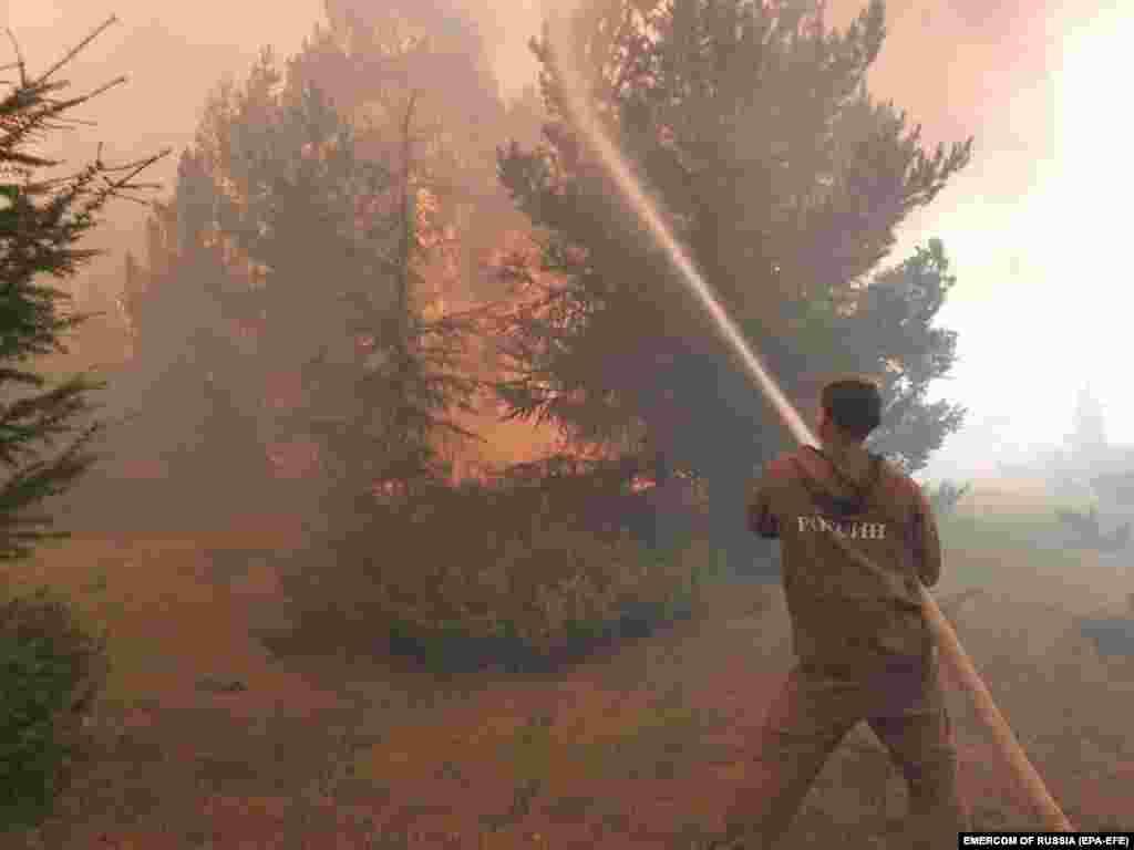 Un pompier ajută la stingerea incendiilor în Republica Sakha (Yakutia), Rusia. Conform datelor operaționale ale ministerului rus de urgență, 163 de incendii sunt active pe teritoriul Republicii Sakha (Yakutia). În total, 4.900 de persoane și 869 de unități de pompieri au fost implicate în stingerea incendiilor forestiere din Yakutia.