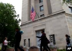 Люди прогуливаются около здания Департамента юстиции США