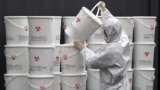 South Korea -- A worker in protective gear stacks plastic buckets containing medical waste from coronavirus patients at a medical center in Daegu, South Korea, Monday, Feb. 24, 2020.