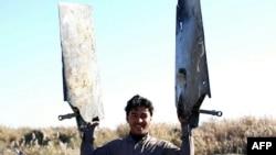 Սիրիա - «Իսլամական պետության» զինյալը ցույց է տալիս Հորդանանի վթարված կործանիչի բեկորները, Ռաքքա, 24-ը դեկտեմբերի, 2014թ․