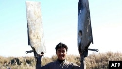 A video grab purportedly showing an Islamic State fighter displaying pieces of a warplane from the US-led coalition that crashed near Raqqa city in Syria.