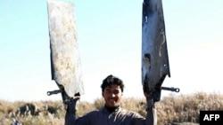"""Кадр видеозаписи, на которой, как предполагается, запечатлен боевик """"Исламского государства"""" с обломками иорданского истребителя, у павшего в районе Ракки, 24 декабря 2014 года."""