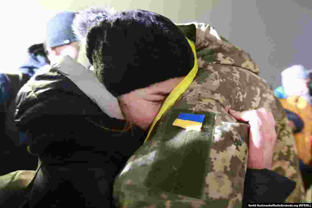 Ukrainian soldiers released by Russia-backed separatists in a prisoner swap are reunited with their loved ones at Boryspil Airport in Kyiv on December 28. (RFE/RL/Serhiy Nuzhnenko)