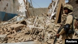 File photo of a Pakistani soldier standing near the debris of a house destroyed during a military operation in the town of Miranshah in North Waziristan.