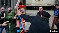 Ukraine -- Members of Crimean self-defence units block a topless activist from the Ukrainian feminist group Femen, who is taking part in an anti-war protest near the Crimean parliament building in Simferopol, March 6, 2014.