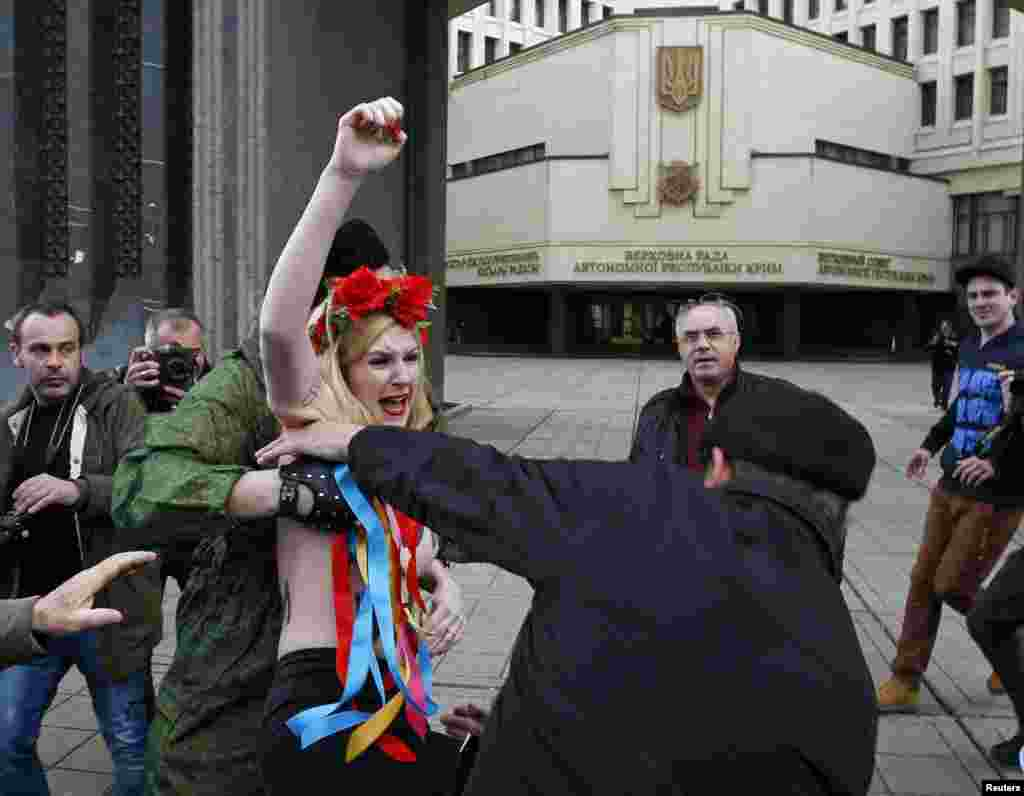 Members of Crimean self-defense units block a topless activist from the Ukrainian protest group Femen taking part in an antiwar protest near the Crimean parliament building in Simferopol. (Reuters/David Mdzinarishvili )
