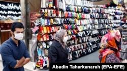 Иранцы в очереди за покупками на улице в защитных масках и перчатках. Тегеран, 18 апреля 2020 года