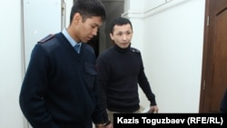 Полиция Әсет Нұржаубайды қолына кісен салып сотқа алып келе жатыр. Алматы, 26 қыркүйек 2018 жыл.