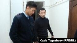 Асет Нуржаубай под конвоем в наручниках перед залом судебного заседания. Алматы, 20 сентября 2018 года.