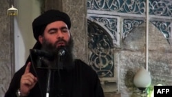 An image grab taken from a propaganda video released on July 5, 2014 by al-Furqan Media allegedly showing the leader of the Islamic State (IS) jihadist group, Abu Bakr al-Baghdadi, at a mosque in Mosul.