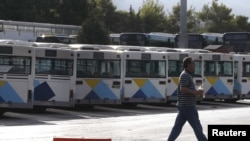 A man walks past buses that are not in operation due to a 24-hour strike in urban transport at a bus station in Helleniko, ,Greece