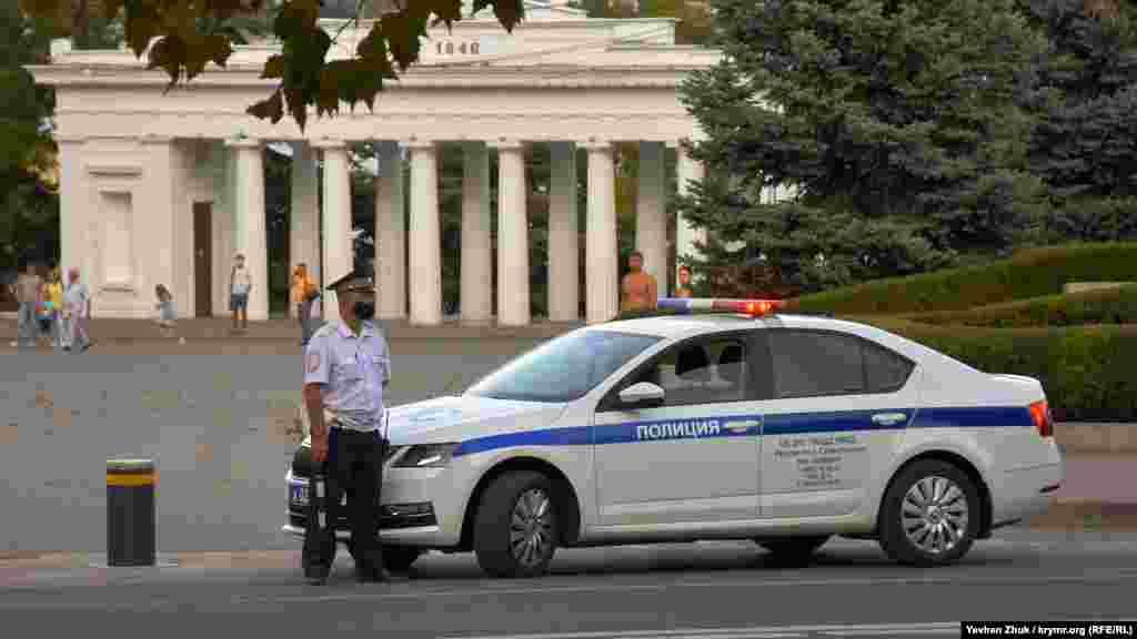 Сотрудник российской ГАИ в защитной маске дежурит на площади Нахимова