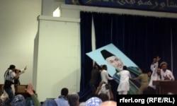 Сторонники Абдуллы Абдуллы снимают со стены портрет уходящего президента Хамида Карзая. 8 июля 2014 года.