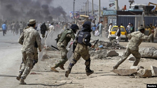 Afghan riot police run toward protesters during a demonstration in Kabul on September 17.