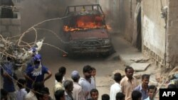Onlookers gather near a burning vehicle in a troubled area of Karachi