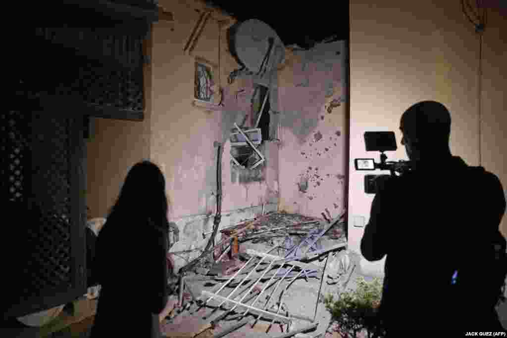 Journalists film a damaged house following a rocket attack fired from the Gaza Strip, in the southern Israeli city of Sderot on May 19, 2021.