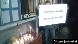 """Молодой человек держит плакат """"Молись за Украину""""."""