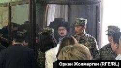 Бывший министр национальной экономики Казахстана Куандык Бишимбаев (за стеклом), обвиненный в хищениях, в суде по его делу. Астана, 7 ноября 2017 года.