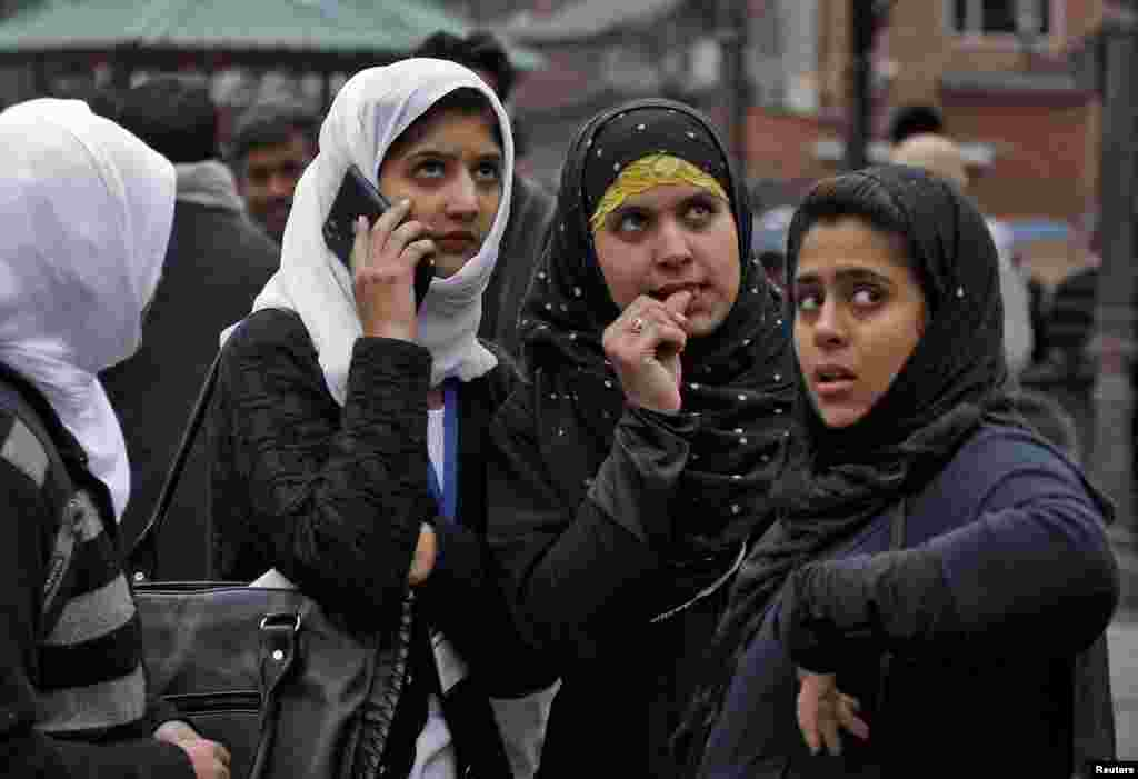 Kashmiri girls stand on a road divider after vacating their office buildings following the earthquake in Srinagar.