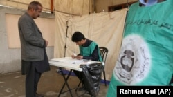 An Afghan employee of the Independent Election Commission registers a voter in Kabul in April.