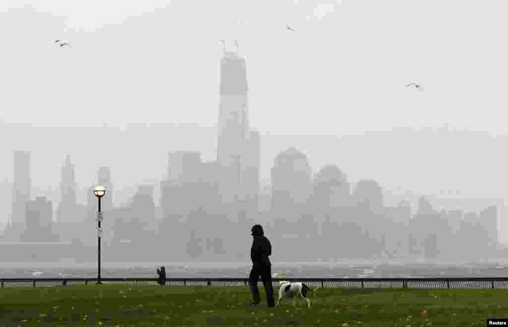 A person walks through a park along the Hudson River across from New York's Lower Manhattan as rain falls in Hoboken, New Jersey.