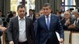 Prime Minister Sadyr Japarov (left) walks with ex-President Sooronbai Jeenbekov in Bishkek on October 16, the day after Japarov took over presidential powers.