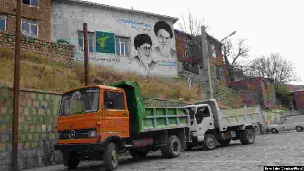 A painted sign shows Iran's supreme leader, Ayatollah Ali Khamenei, and his predecessor, Ayatollah Ruhollah Khomeini.