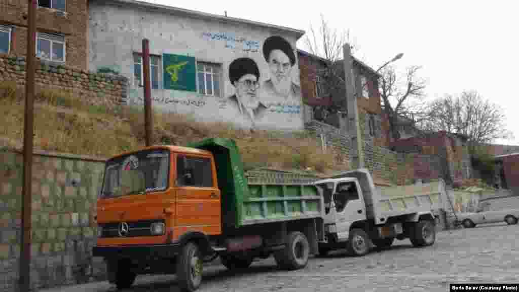 A painted sign shows Iran's supreme leader, Ayatollah Ali Khamenei, and his predecessor, Ayatollah Ruhollah Khomeini.